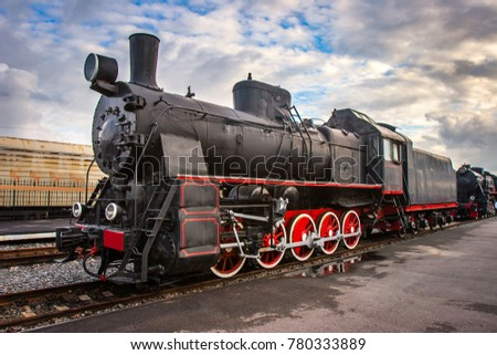 Steam locomotive with red wheels. Retro locomotive on rails. Black locomotive.