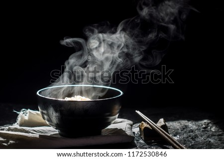 Steam of hot soup with smoke in a soup black ceramic bowl on dark background.selective focus.
