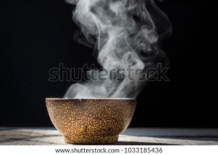 Steam of hot soup with smoke wood bowl on dark background.selective focus