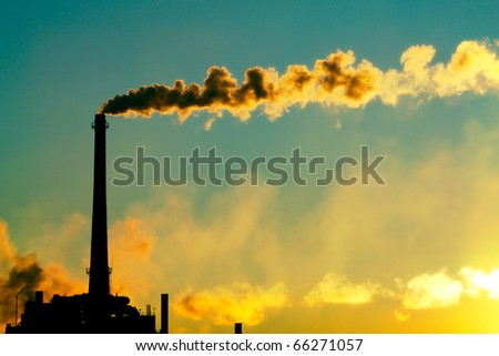 Steam rises from a smokestack on a factory silhouetted against the sunlight.