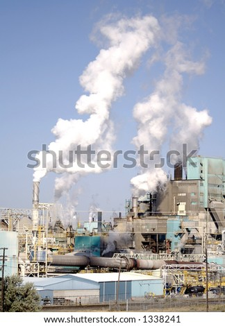 Steam rises into the sky from the stacks of an industrial manufacturing complex