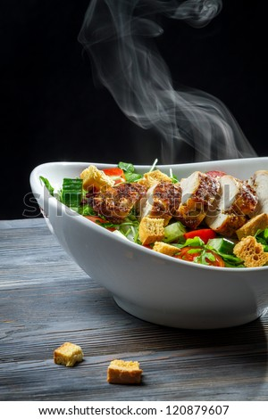 Steam rising from a freshly roasted chicken on salad