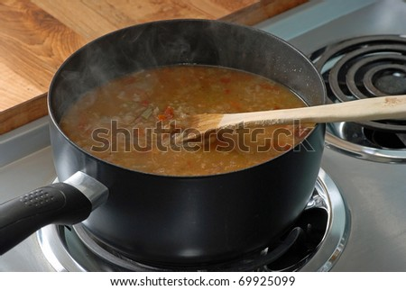Steam rising from boiling pot of chicken and sausage gumbo.