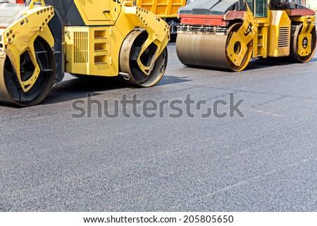 Steam road rollers compacting fresh asphalt during road repairing works