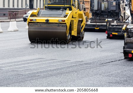 Steam roller machines compacting fresh asphalt during road repairing