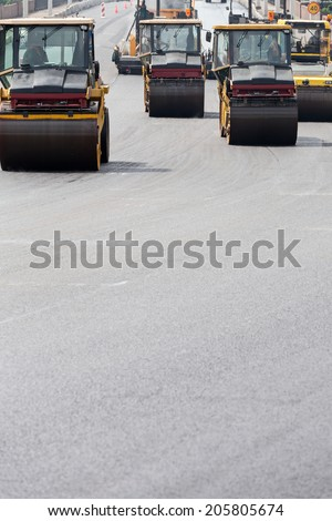 Steam rollers machines compacting fresh asphalt during road construction works