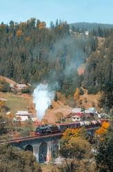 Steam train in old stone bridge in mountain village. Black steam loco with cargo carriages passes through old stone viaduct in mountain pass in autumn. Vertical photo with smoke