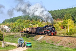 Steam train in village near to bull, old car and tractor. Province romance. Black steam loco with smoke and freight wagons. Three types (modes) of transport. Nostalgic fairy tale