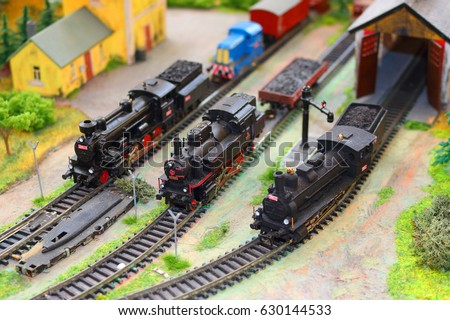 Steam trains on miniature railway train station model. Handmade railways model.