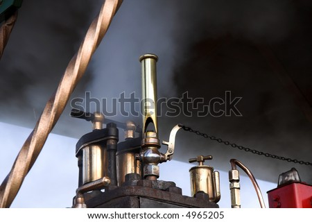 Steam whistle and smoke under the roof of a vintage traction engine