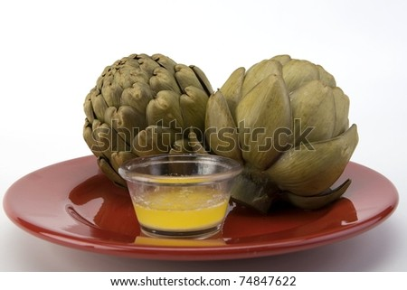 Steamed artichoke with melted butter on a red ceramic plate.