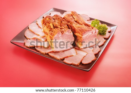 Steamed bacon on a plate and red background
