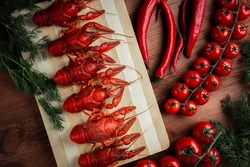 Steamed boiled crawfish on a chopping Board. Crayfish with herbs pepper and tomatoes