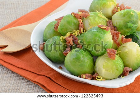 Steamed brussels sprouts with crisp bacon bits and fresh lemon zest in white serving dish
