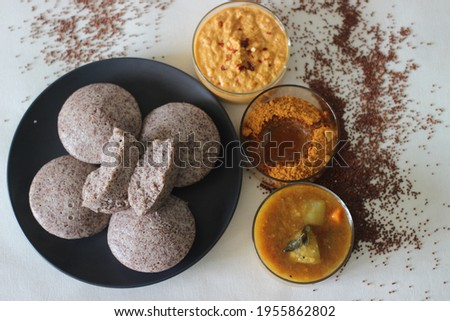 Steamed cakes made with finger millets and skinned black gram. Locally known as Ragi idli. Served along with coconut chutney and sambar. Shot on white background. Foto stock ©