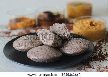 Steamed cakes made with finger millets and skinned black gram. Locally known as Ragi idli. Served along with coconut chutney, sambar and red fish curry. Shot on white background. Foto stock ©