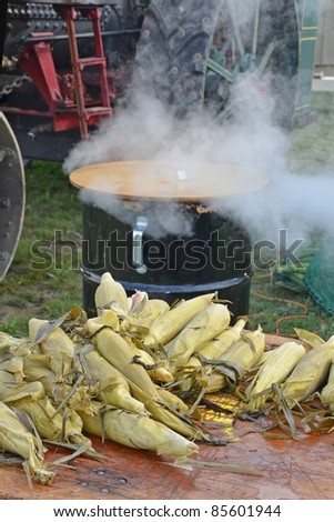 steamed corn on the cobs laying on a wooden table, steaming kettle with emerging steam in the background