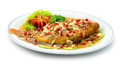 Steamed Fish with Lime Sauce Spicy Tasty (Red Tilapia Fish) Thai Food famous dish of Asian Delicious food Healthy decorate carved chili and Vegetable sideview