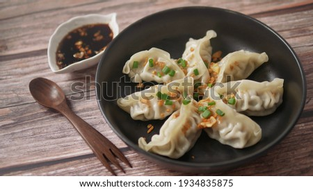 Steamed Gyoza or dumpling stuffed ground pork dipping with garlic soy sauce, famous Chinese appetiser. Stock photo ©