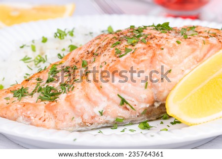 Steamed salmon with fresh herbs and lemon. Rice as a garnish #235764361