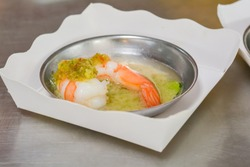 Steamed shrimp with seafood sauce and Thai herb in metal bowl on white paper plate in chinese restaurant.