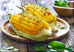 Steamed sweet corn with ingredient herb on wooden plate