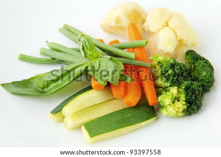 steamed vegetables of yellow, green and orange colors on white background