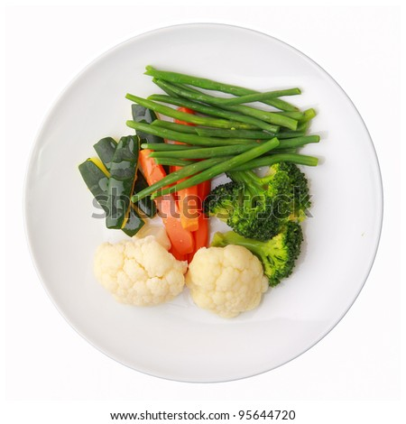 steamed vegetables of yellow, green and orange colors on white round dish isolated over white background. top view.