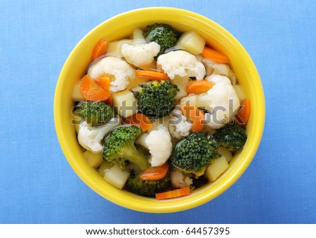 Steamed vegetables with broth in yellow bowl. - stock photo