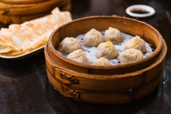 Steamed Xiao Long Bao (Soup Dumplings) in The Bamboo Basket. Served in Restaurant in Taipei, Taiwan.