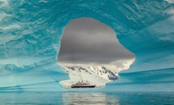 Steamer ship seen through the hole in the iceberg at Antarctic peninsula