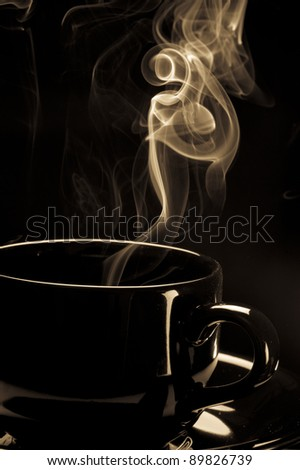 Steaming black coffee cup on black background