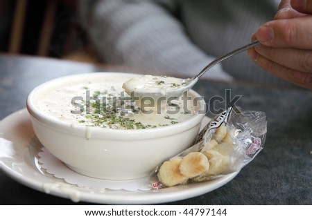 Steaming bowl of white New England clam chowder with crackers on the side