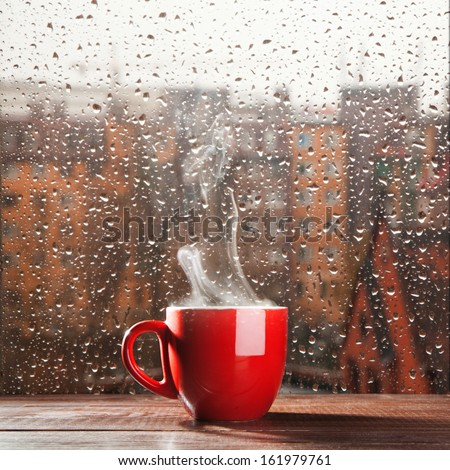 Stock Photo Steaming coffee cup on a rainy day window background