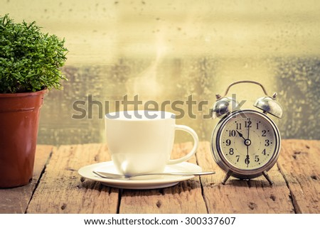 Steaming coffee cup on a rainy day window background,good time of coffee