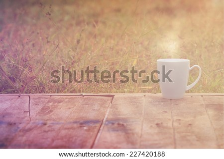 Steaming coffee cup on wood table. grass background