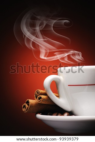 Steaming cup of coffee, cinnamon sticks and coffee beans. - stock photo