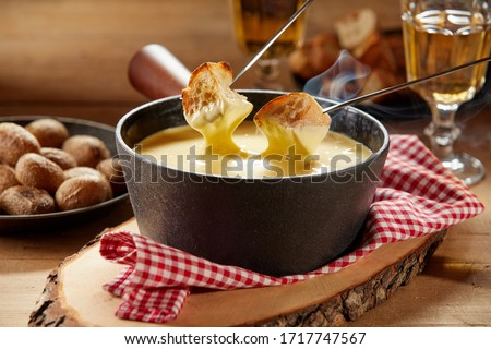 Steaming hot cheese fondue served with wine and toasted baguette on forks for dipping in close up on a rustic table