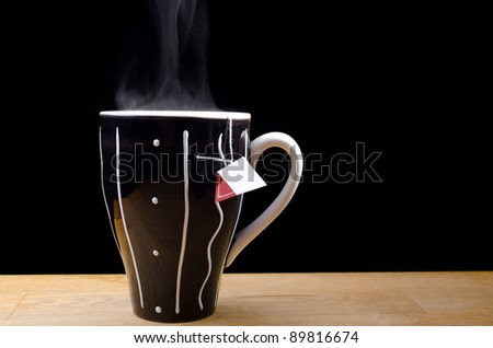 Steaming hot cup of tea on a table with black background