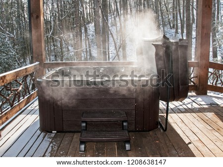 Steaming hot tub on deck with snow in background