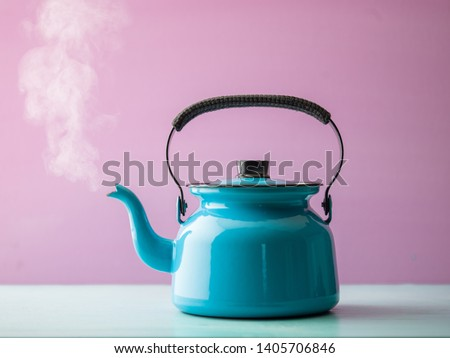Steaming kettle with boiling water against pink background