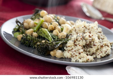 Steaming plate of broccoli and chickpeas served with bulgar and quinoa mix.