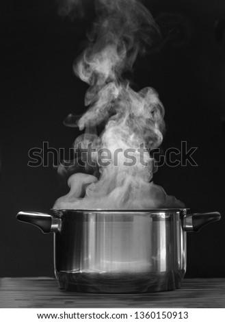 Steaming pot on black background. Smoke above boiling soup pot.