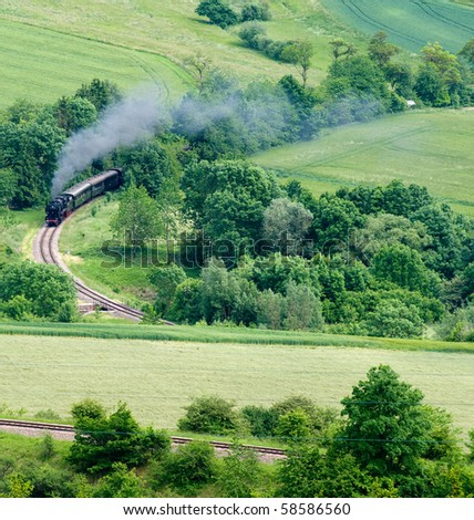 steaming railway locomotive blows through green landscapes