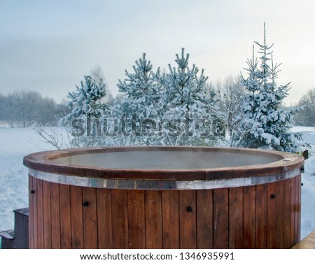 Steaming wooden hot tub with spa in winder with  snow and frosty Christmas trees in background - Image #1346935991