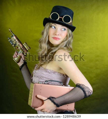 Steampunk girl with pistol and small suitcase to look back