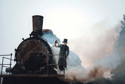 Steampunk man in a hat with a kerosene lamp in his hand stands on top of an old locomotive. Retro trip. Rusty the steam train. Fantastic locomotive of the last century.