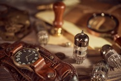 Steampunk still life - old vintage objecys on a wooden background. Leather wrist watch, dark glasses, aold tube lamps, magnifying glass, gears