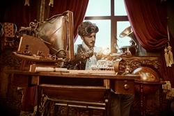 Steampunk world. Intelligent steampunk man scientist inventing something in his laboratory. Victorian interior.