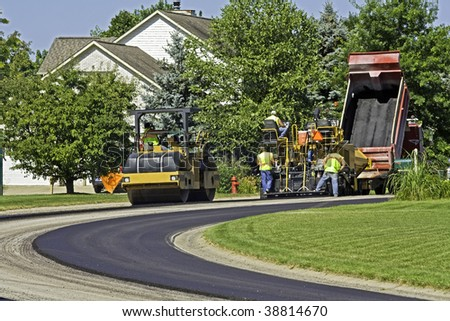 Steamroller and dump truck crews laying new pavement in a residential neighborhood